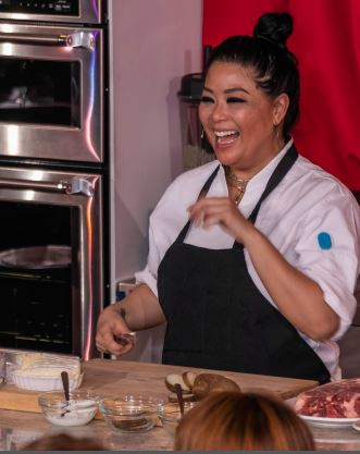 Chef Mar enjoys a laugh with dinner guests as she demonstrates a four-course meal