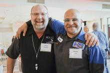Ford Asset Instructor Brian Thompson smiling with Foundation Scholar Ronnie Larry at the Foundation's Annual Breakfast.